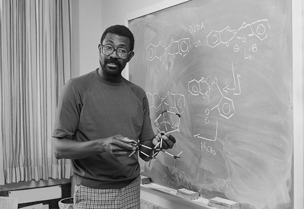 Professor Slayton Evans standing in front of a chalkboard holding a chemistry model